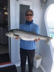 Bobby Baek, Palisades Park, with a striped bass landed