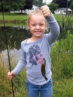 Xoie Barr, 7, shows off a bluegill she caught during the Swarthout Bait & Tackle Shop Take a Child Fishing Derby.