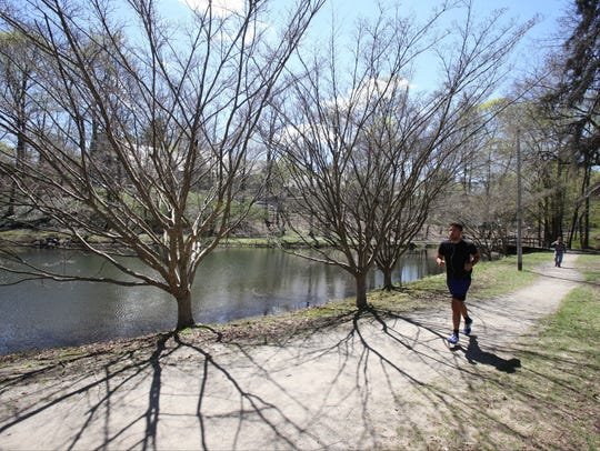 """A a jogger runs along the Bronx River Pathway north of Greenacres Avenue in Scarsdale. The Westchester County village ranks No. 2 on the annual """"Bloomberg Richest Places"""" index."""