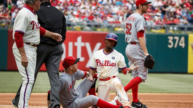 Phillies shortstop Jimmy Rollins (center right) reacts to getting tagged out by Reds third baseman Todd Frazier (center left) on a fly out by Chase Utley during the third inning Sunday.