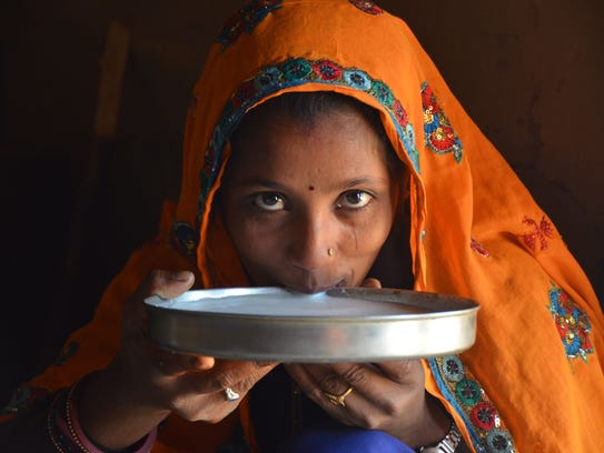 A woman drinks fresh buffalo milk in a small Indian
