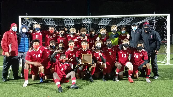 The Holland boys soccer team celebrates winning the OK Green Conference championship on Monday night at Holland.