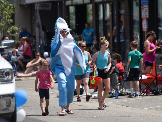 A man in a shark suit waves to the crowd during Saturday's Granite City Days Parade in St. Cloud.