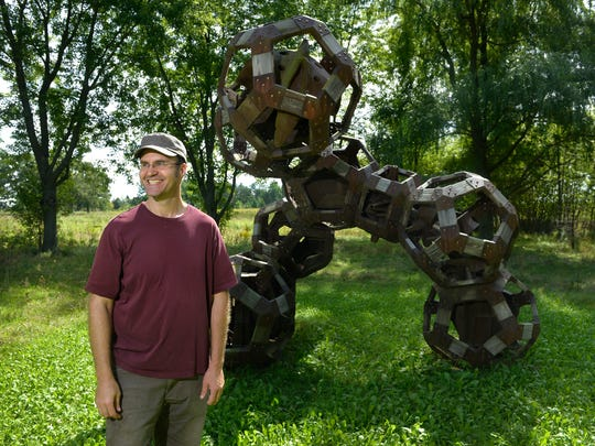 Artist Sam Spiczka smiles as he talks about his work at his rural Sauk Rapids home in this 2016 photo. Spiczka lost the tips of the four fingers of his left hand in a tragic lawnmower accident that he says will not keep him from continuing his artwork.