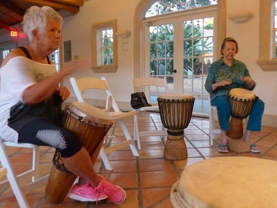 Gay MacDonald, left, and Jo Petersen learn hand drumming