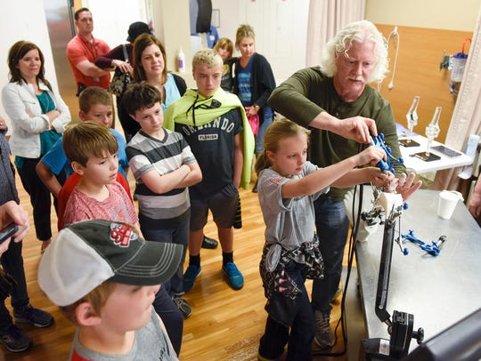 Dr. Eric Green lets students try a robotically controlled