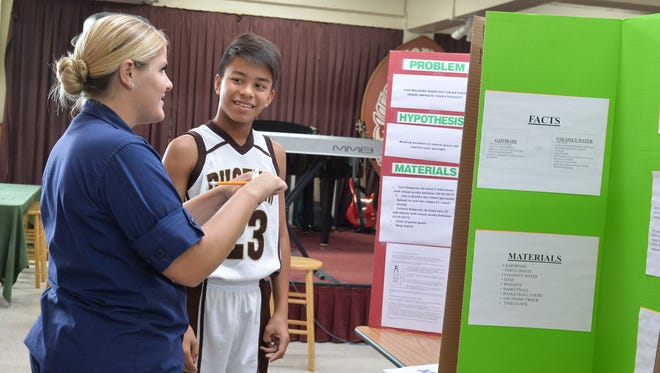 """Students present their projects to judges during the 2018 science fair at the Mount Carmel Catholoc School in Agat on April 26, 2018. The theme for the science fair is """"Healthy Living."""""""