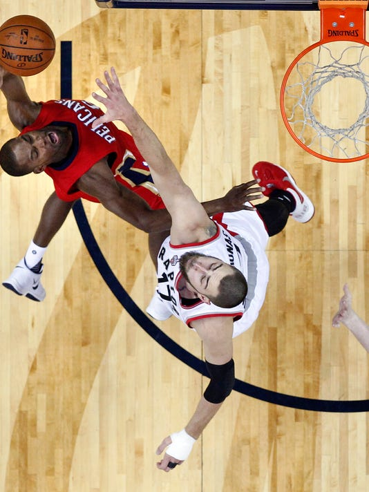 New Orleans Pelicans guard Toney Douglas, left, goes to the basket against Toronto Raptors center Jonas Valanciunas in the first half of an NBA basketball game in New Orleans, Saturday, March 26, 2016. (AP Photo/Gerald Herbert)