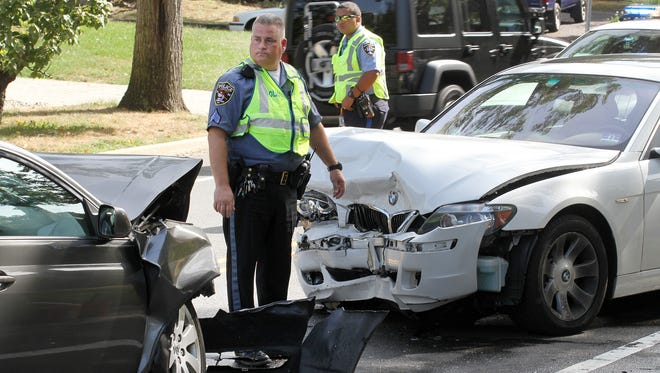 A Brick Township police sergeant stands between the two vehicles involved in a head-on collision on Princenton Avenue at East Avenue Tuesday morning, September 29, 2015.  At least one injured person was transported to Jersey Shore University Medical Center for treatment by the Brick First aid.