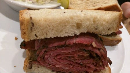 TooJay's hot pastrami sandwich comes with French fries, coleslaw and a pickle.
