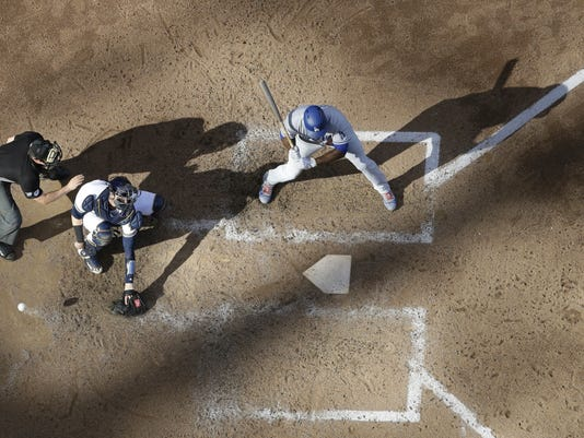 Milwaukee Brewers catcher Jett Bandy can't handle a pitch from relief pitcher Jared Hughes with Los Angeles Dodgers' Yasiel Puig at bat during the sixth inning of a baseball game Saturday, June 3, 2017, in Milwaukee. Chris Taylor scored from third. (AP Photo/Morry Gash)