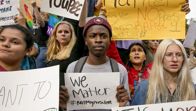 Protestors, from left, Celeste Ramirez, 20, Erin Ckodre , 21, Ronald Elliott, 18, Patricia Romo, 22, and Rose Ammons, 18, hold up signs at Texas State University in San Marcos, Texas, Thursday Nov. 10, 2016, in opposition of Donald Trump's presidential election victory. (Jay Janner/Austin American-Statesman via AP)