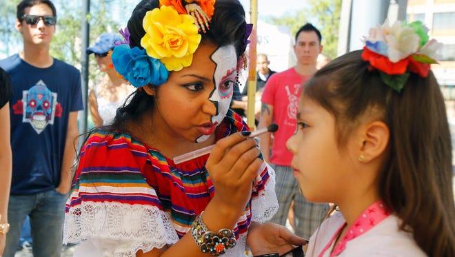 Artist Desiree Salas paints the face of Emily Jeronimo at Mesa Arts Center.