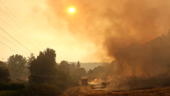 Firefighters work to protect homes east of Santa Rosa, Calif., on Oct. 11, 2017.