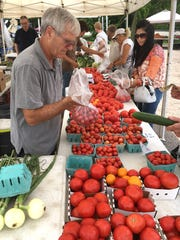 Dwight Carpenter of Carpenter's Farm in Allen, MI, bags up some early-season tomatoes. The market, that runs from 8 a.m.-3 p.m. on Thursdays takes place at the southwest corner of Seven Mile and Center in Northville.