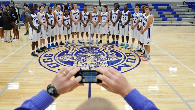 Hume-Fogg basketball coach David Givens takes a picture of his team on the floor of the high school's new gym, which was dedicated Thursday in downtown Nashville.