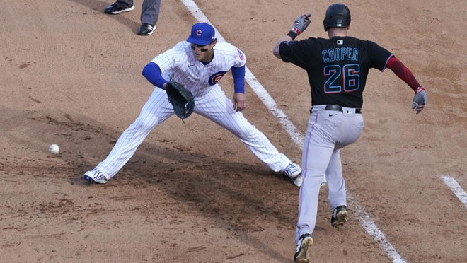 Miami Marlins' Garrett Cooper (26) grounds out as Chicago Cubs first baseman Anthony Rizzo handles the throw during the ninth inning in Game 2 of a National League wild-card baseball series Friday, in Chicago.