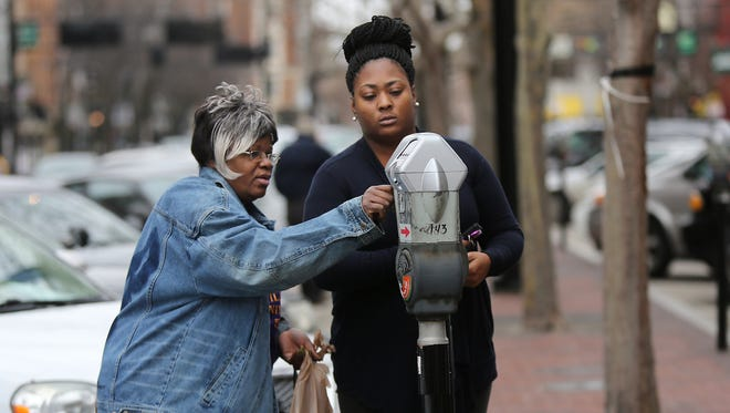 Brittany Toler, right, and Flora Amison, both from North College Hill, feed their parking meter Downtown last winter.