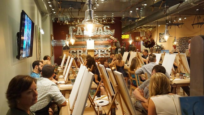 Canvas & Grapes guests receive painting instruction in the unique paint & sip provider's cozy class setting.