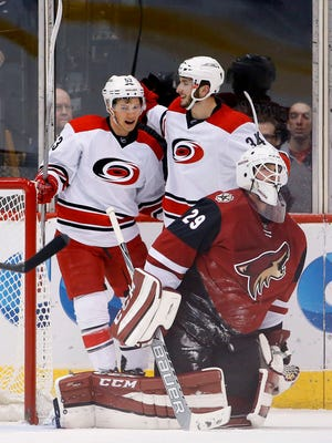 Carolina Hurricanes' Phil Di Giuseppe (34) celebrates his goal against Arizona Coyotes' Anders Lindback (29) with teammate Jeff Skinner (53) during the second period of an NHL hockey game Saturday, Dec. 12, 2015 in Glendale, Ariz.
