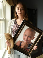 Fifteen-year-old Jacalyn Lambrix holds a picture taken in 2009, when she was six-years-old and going through cancer treatments.  She had Wilms tumor, a rare form of cancer which she has now beaten twice.   Now five years cancer-free, the Grand Ledge High School pompon team member is currently a prospering student who one day hopes to dance at MSU.