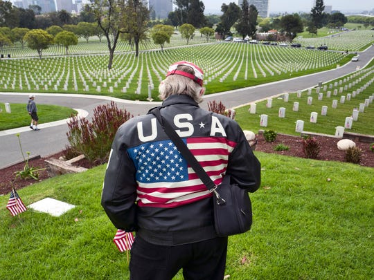 Mike Lackey pays his respects to fallen soldiers on Memorial Day at the Los Angeles National Cemetery in Los Angeles on Monday, May 28, 2018.