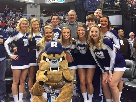 John Seal (middle) poses with the Butler cheer team before a game at Bankers Life Fieldhouse.