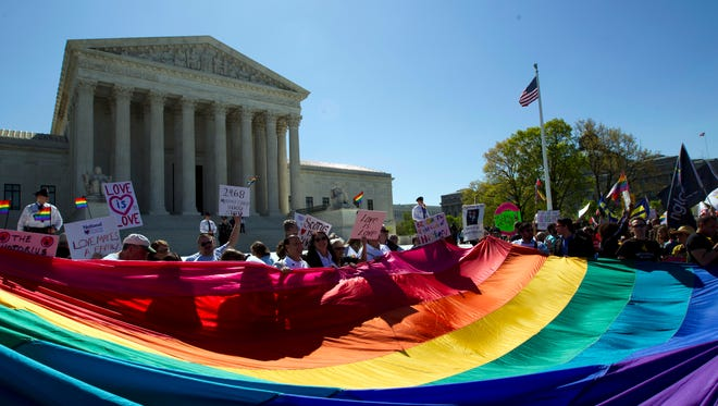 In this April 28, 2015 file photo, demonstrators stand in front of a rainbow flag of the Supreme Court in Washington.