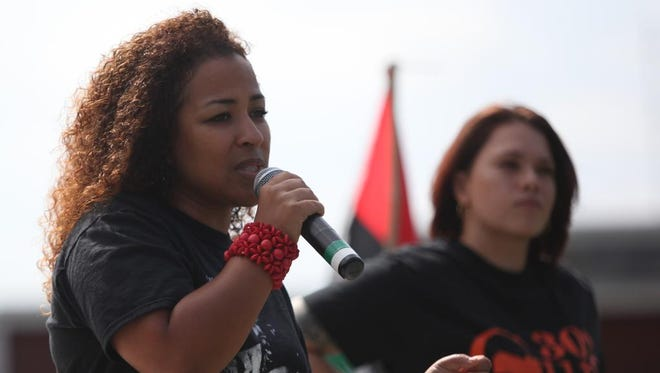Chandra Pitts (left) with One Village Alliance speaks Sunday at a rally for gun awareness at Judy Johnson Park in Wilmington.
