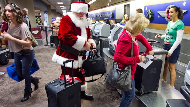 Holiday travelers, including Donald Occimio of Mesa, Ariz., dressed as Santa Claus, and his wife Diane check in with customer service agent Angelee Arciniega, right, for their Southwest Airlines flight at Sky Harbor International Airport on Dec. 21, 2011, in Phoenix.