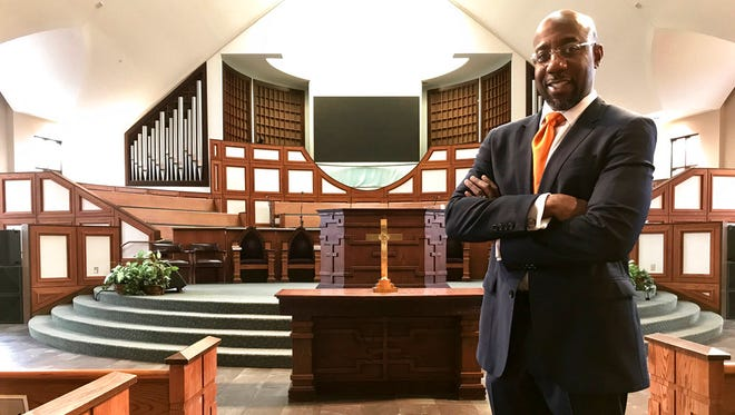 The Rev. Raphael Warnock stands in the sanctuary of Ebenezer Baptist Church in Atlanta. Warnock is senior pastor of the congregation once led by the Rev. Martin Luther King Jr., Thursday, Jan. 11, 2018 photo,