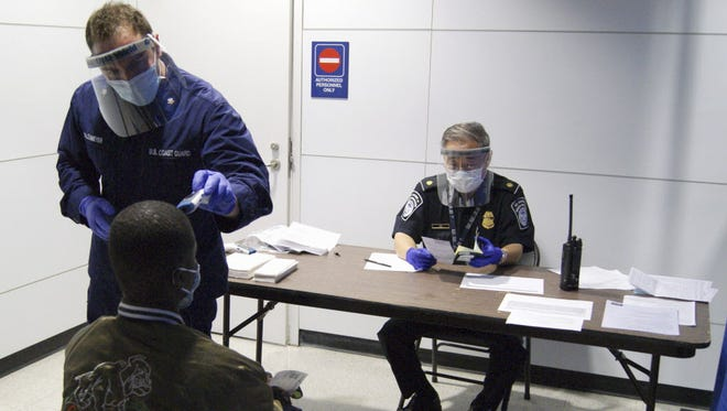 On Oct. 16, U.S. Coast Guard Health Technician Nathan Wallenmeyer, left, and Customs and Border Protection Supervisor Sam Ko, right, conduct pre-screening measures on a passenger from Sierra Leone at O'Hare International Airport's Terminal 5 in Chicago.