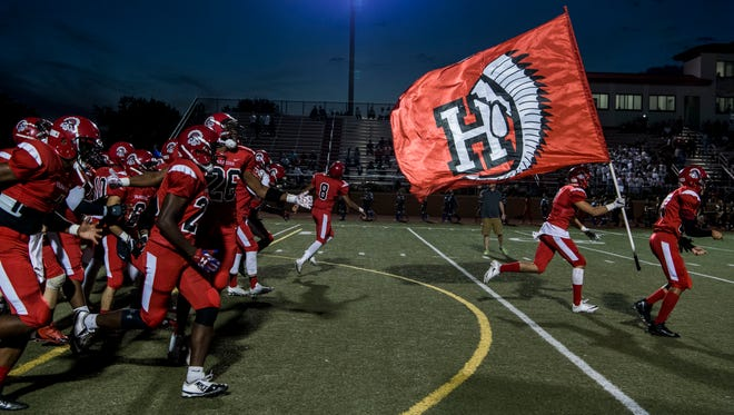 The Harrison Warriors rush onto the field before the game against the Castle Knights at Romain Stadium in Evansville, Ind., Friday, Sept. 29, 2017.
