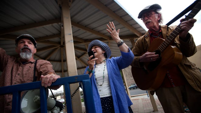 At center, Jane Voss and Hoyle Osborne, right, perform during a vigil for Charlottesville, Virginia violence victims Tuesday at Orchard Park in Farmington.