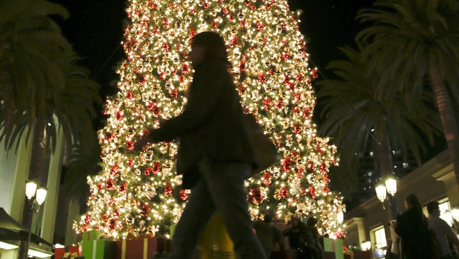 A holiday shopper walks past a large Christmas tree at Fashion Island shopping center in Newport Beach, Calif.