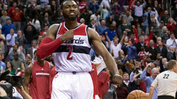 Wizards guard John Wall celebrates after scoring the game-tying basket during the second overtime against the Boston Celtics on Monday night.