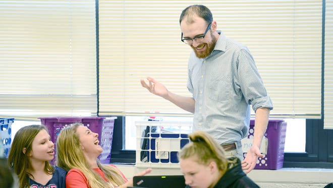 Students Katlyn Howard, 13, left, and Makayla Littrell, 13, laugh with seventh-grade math teacher Doug Cutshall as he teaches the class about percentages and how they relate to sales tax during his class at Erwin Middle School on March 31. Cutshall says the program made him a better teacher than he would have become without it.