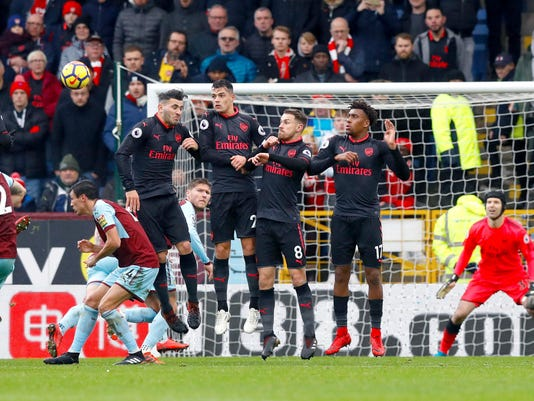 Burnley's Robbie Brady, left, takes a free kick, during the English Premier League soccer match between Burnley and Arsenal, at Turf Moor, in Burnley, England, Sunday Nov. 26, 2017. (Martin Rickett/PA via AP)