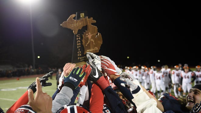Livonia Franklin players hoist the regional championship trophy after defeating Flushing 31-29.