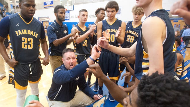 Fairdale head basketball coach David W. Hicks, II joins hands with his team during a time-out on the second day of the boys' LIT. Jan. 9, 2018