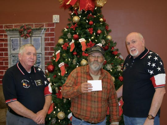 Harold Straley, left, and Bill Oskin, right, present Dan Duke with a gift card to help him buy prescription medications.