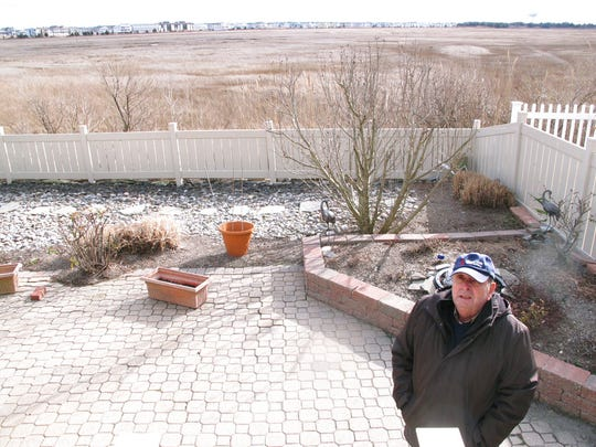 Marty Mozzo poses in his backyard in Ocean City on the edge of a back bay wetlands in February 2016. When he and his wife were considering buying the house, they looked at a small trickle of water in the distance and wondered if the property would flood, deciding the water was too far away to pose a danger. Within weeks, their house was surrounded by floodwaters.