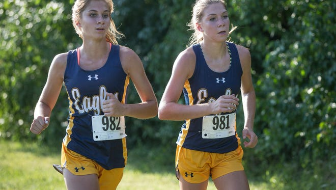 Brittany and Brandy Tuttle, twin sisters running for Delta High School, start off the county cross country meet together Tuesday evening at Cowan High School. The two finished 5th and 6th in the meet.