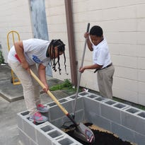 Children from the Boys and Girls Club of Opelousas help lay down the soil for a garden they will use to grow fruit and vegetables.