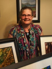 Joan Volkman poses amid her alcohol ink paintings.