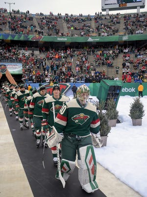 Minnesota Wild goalie Devan Dubnyk leads his team out for warmups before an NHL Stadium Series hockey game against the Chicago Blackhawks at TCF Bank Stadium, Sunday, Feb. 21, 2016, in Minneapolis. (AP Photo/Craig Lassig)