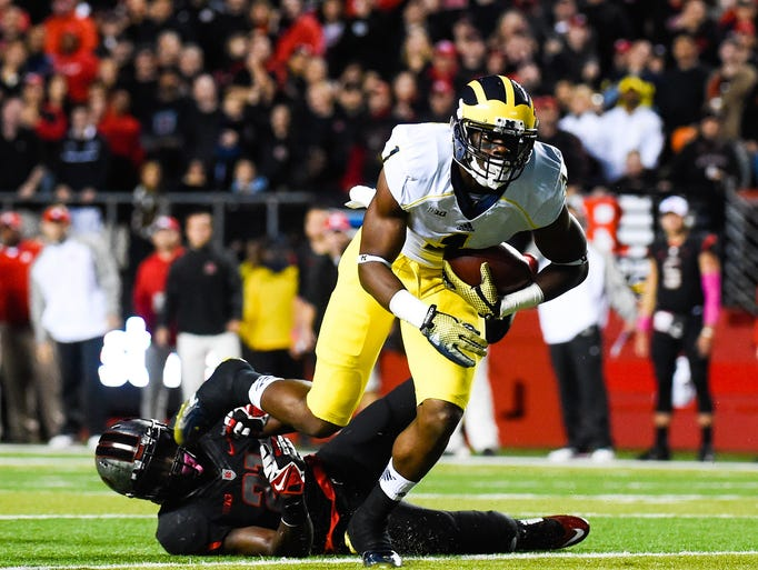 Michigan receiver Devin Funchess, top, rushes past Lorenzo Waters of the Scarlet Knights in the first quarter at High Point Solutions Stadium.