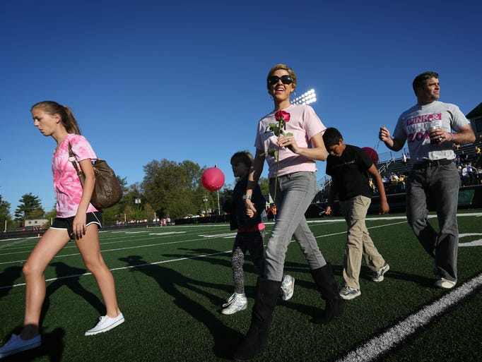 "Cancer patient Jill Conley, center, takes the field before a Pink & White ""powder puff"" football game at Trinity High School to benefit breast health care. After a rough winter that reminded her of her imminent mortality, cancer patient Jill Conley has recently experienced a burst of energy that has allowed her to be more active with her charity Jill's Wish. Apr. 25, 2014."