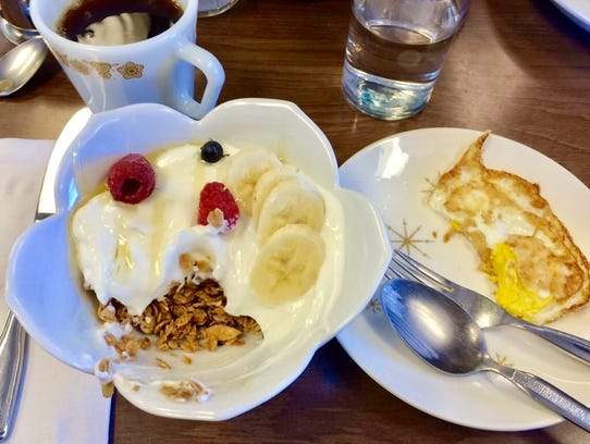Granola with fruit and honey, and a side of eggs at