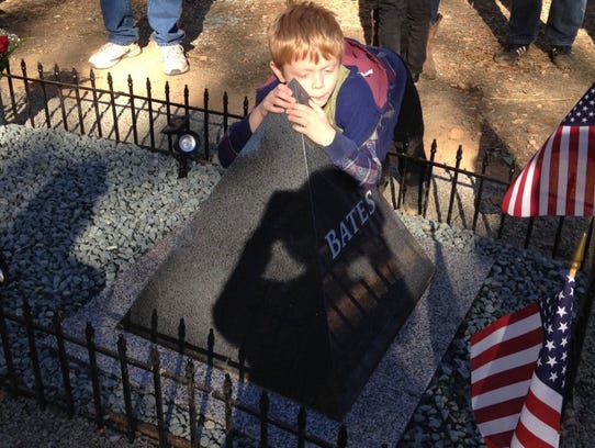 Gunner Bates, 6 at the time, embraces the headstone